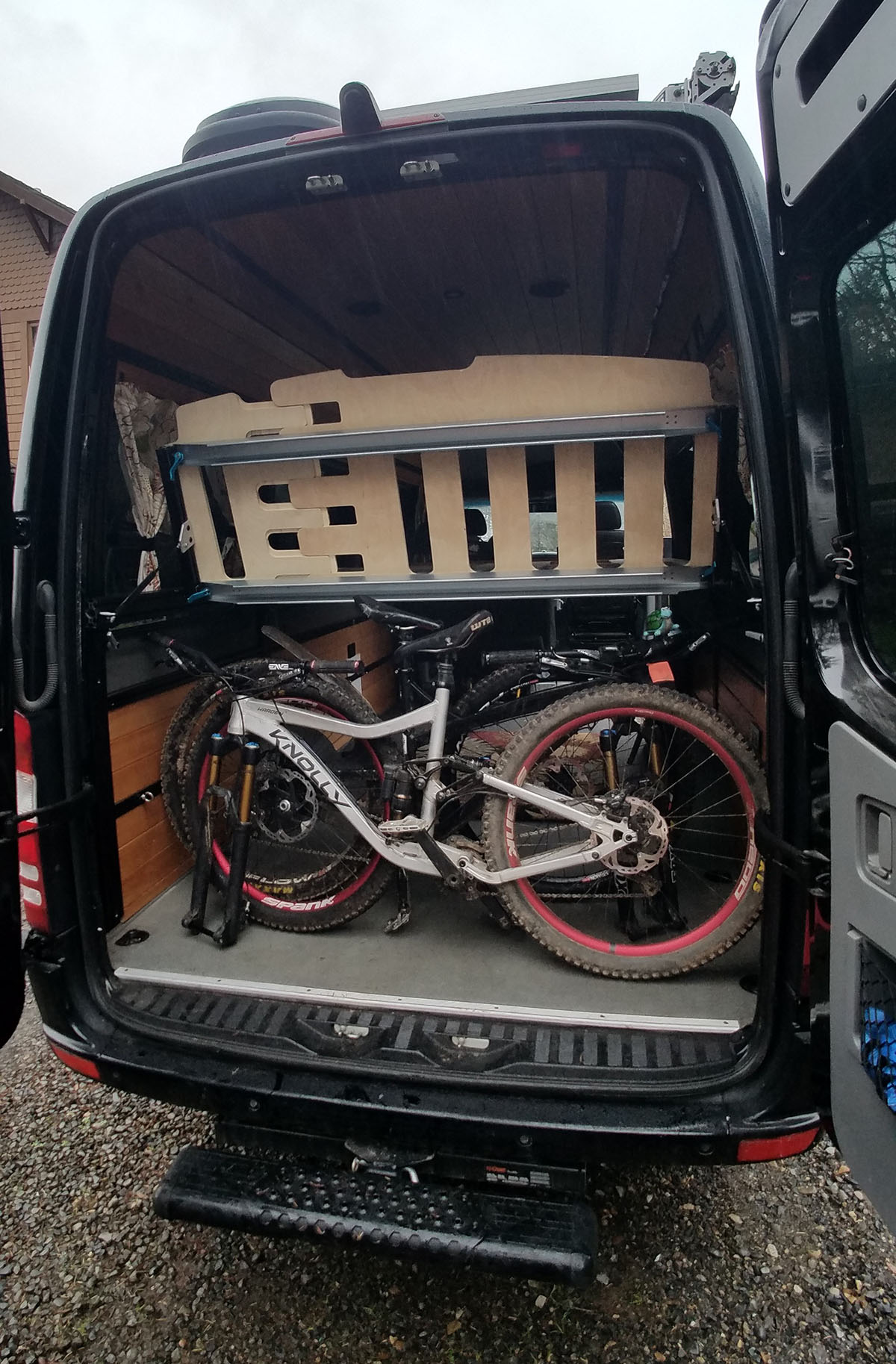 Sprinter van, with bikes; shown with adjustable bed tilted up for access